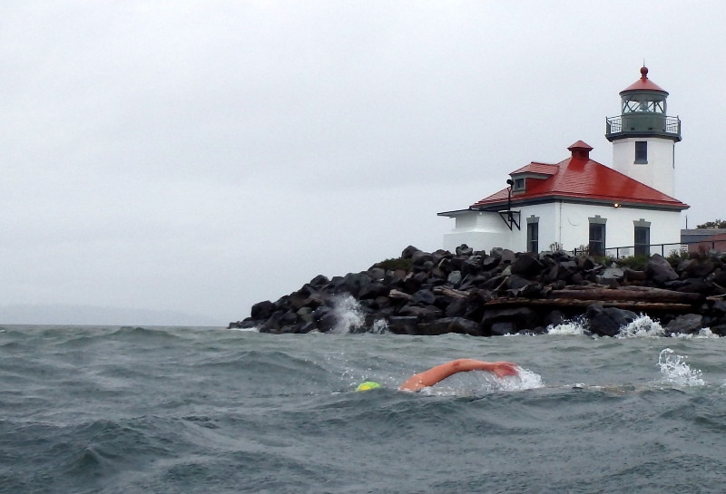 Swimming past Alki Light during storm